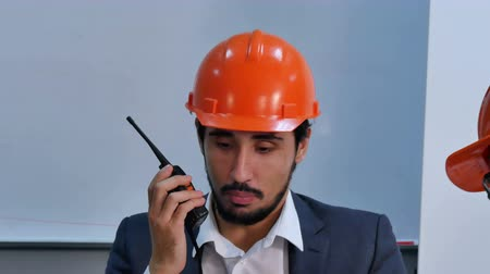 işlenmiş : Businessman in helmet talking at radio set sitting in office