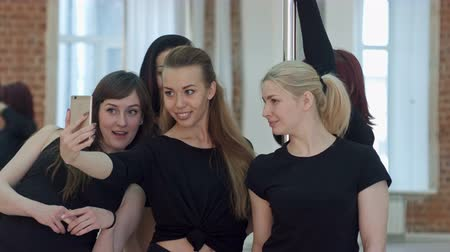 striptease : Group of beautiful young women taking a selfie during a break on a pole fitness class Stock Footage