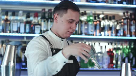 шейкер : Expert barman is making cocktail at night club