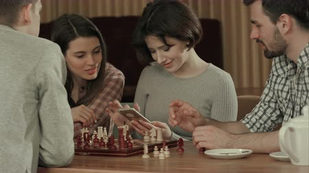 tactic : Group of young people playing chess and using smartphone