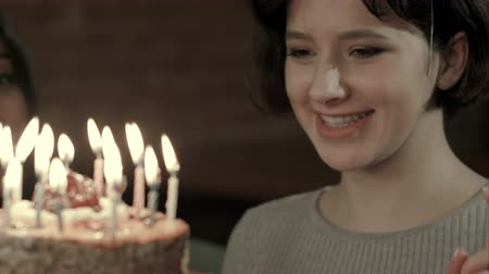veselí : Young attractive girl is about to make a wish and blow all candles Dostupné videozáznamy