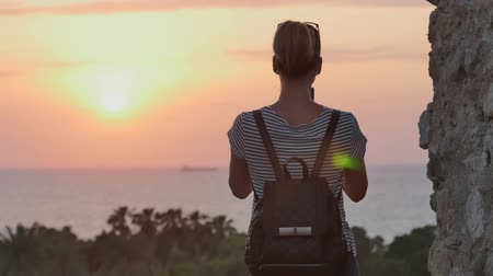 izrael : Female traveler with backpack taking photo of sunset sea on her phone