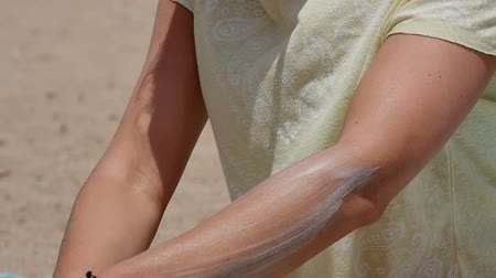 sunblock : Woman spreading sunscreen on her arm at the beach on a hot sunny day