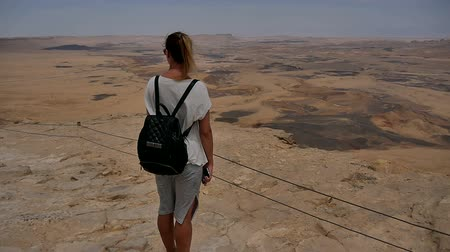 dağcı : Young woman with backpack standing on cliffs edge and enjoying the desert view