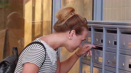 mailbox : Pretty young woman checking her mailbox for new letters Stock Footage