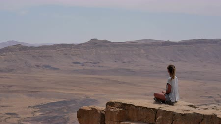 izrael : Young woman in sunglasses sitting on cliffs edge and looking around the desert Stock mozgókép