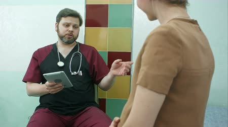 gynaecology : Happy doctor having a cunsultation with pregnant woman, using digital tablet Stock Footage