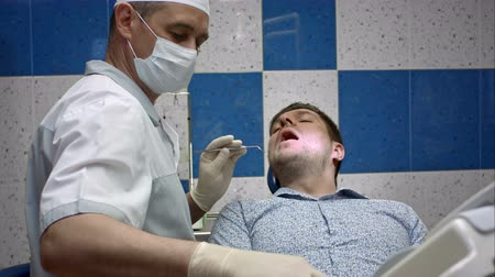 professionalism : Young male patient repairing teeth in dental clinic Stock Footage