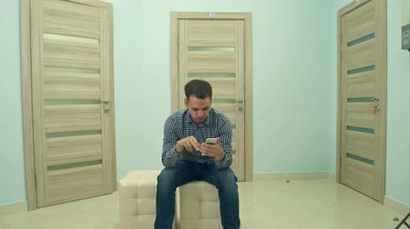 терпение : Male patient using phone while waiting for his doctor appointment