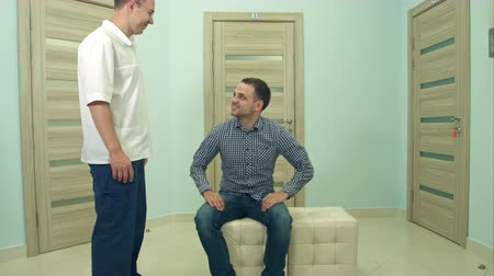 unalom : Male doctor inviting male patient to his office Stock mozgókép