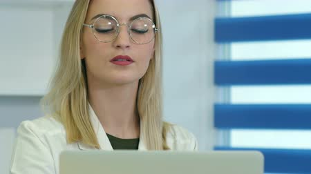 ceket : Concentrated female doctor in glasses working on laptop at reception desk