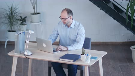 one by one : Handsome businessman working with laptop in office Stock Footage