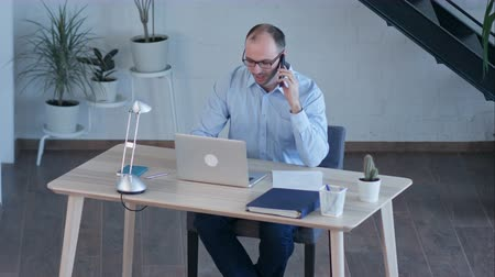 padlástér : Businessman work on computer while talking on smart phone