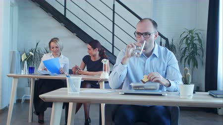 notion : Young businessman eating at break in office drinking water
