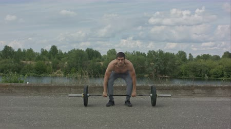 undershirt : Man working out outdoors with barbell