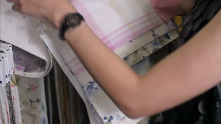 color swatch : Young woman choosing interesting fabric in textile shop Stock Footage