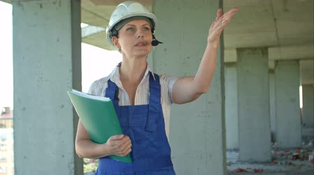 discutir : Builder supervisor oversees building site and gives instructions to workers over the intercom Stock Footage