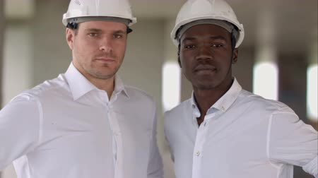 built up : Two engineers, a caucasian and an african american, posing looking to the camera