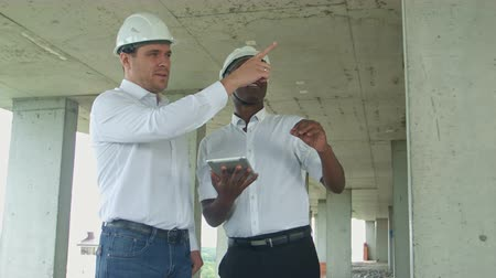 discutir : Executive team on construction site reviewing with tablet formal dressed people reading construction tablet in front of building Vídeos