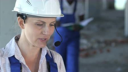 hardhat : Construction team will consult and consider plans for the construction Stock Footage