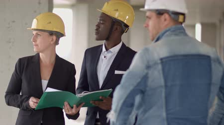 workgroup : Business people group on meeting and presentation in construction site with construction engineer architect and worker looking building model and blueprint plan blueprint plans Stock Footage
