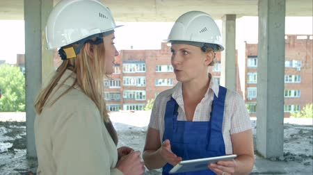 colaboração : Female engineer and worker on construction site with plan on digital tablet
