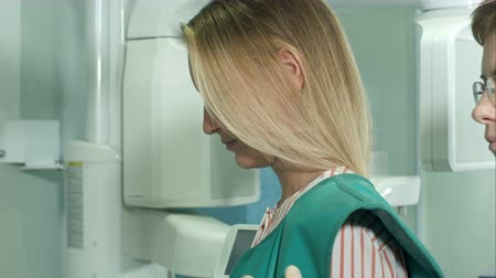рентгенологическое : Young attractive female patient being prepared for dental X-Ray scan