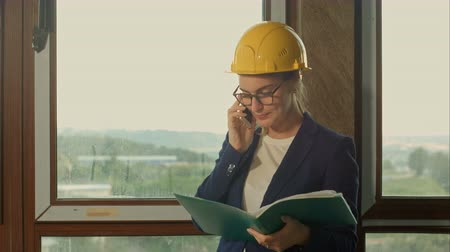 pracownik budowlany : Engineer at a construction site making a business call