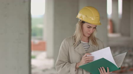 осмотр : Young female architect construction engineer at a construction site eximaining documents