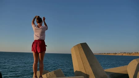 Beautiful fit girl in shorts dancing on concrete blocks near the sea Stok Video