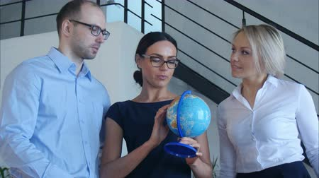aritmética : Three teachers discuss something with globe