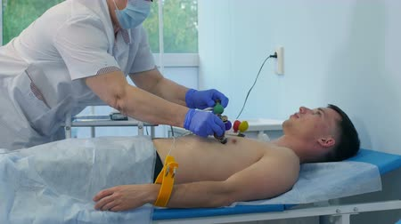 gravador : Nurse attaching ECG electrode pads to male patients chest Stock Footage