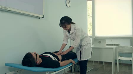 Female doctor doing abdominal examination on male patient Stok Video