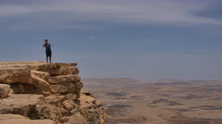 Young man standing on cliff edge and taking pictures of the desert on his phone 影像素材