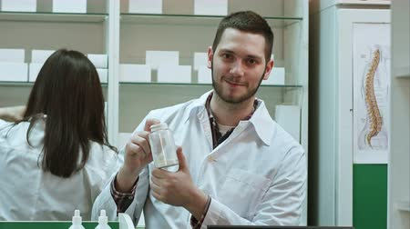 Young malepharmacist holding a white blank bottle of pills, promoting medicine, while his colleague working Stok Video
