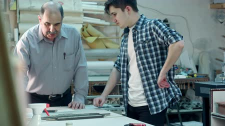 Senior male worker instructing young trainee how to construct a frame behind the desk in frame workshop