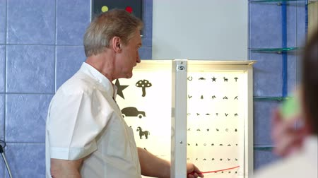 Elderly male ophthalmologist pointing at letters of eye chart