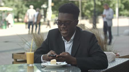 Handsome young afro american businessman using smart phone, messaging his girlfriend, eating at cafe