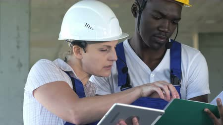 Two workers having conversation and using tablet computer