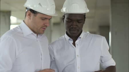 Executive team on construction site formal dressed people reading construction tablet in front of building Stok Video