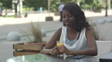 komoly : Portrait of young african woman sipping orange juice and dreaming, while sitting in cafe