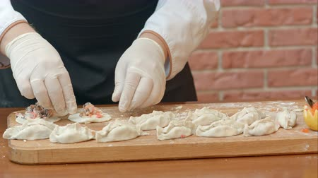 Male hands making homemade dumplings pastry tortellini or ravioli. Model for home made pasta filled with seafood