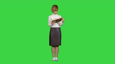 Woman standing and reading book on a Green Screen, Chroma Key