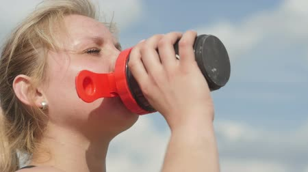 Female drinking a bottle of water after sport Stok Video