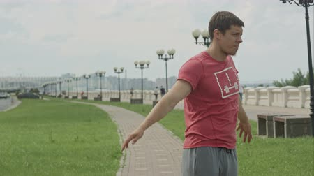 Handsome athlete warming up before jogging outdoors Stok Video