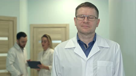 Male doctor looking at camera while medical staff working on the background