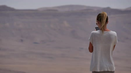 Young woman taking panoramic photo of the desert crater on her phone Stok Video