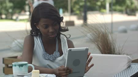 veranda : African american woman have video conferance on her tablet sitting in outside cafe Dostupné videozáznamy