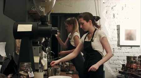 portafilter : Two young female barista working in coffee shop, pareparing coffee Stock Footage