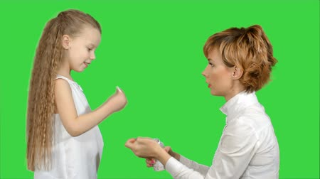puericultura : Mother giving her daughter medicine on a Green Screen, Chroma Key